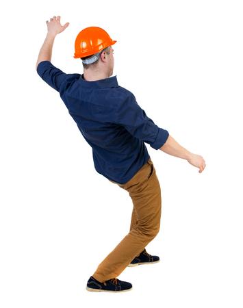 hombre cayendo: Equilibrio joven. o esquivar el hombre que cae. trabajador de la construcción del casco cae. Vista posterior recogida de las personas. trasero vista de la persona. Aislado sobre fondo blanco. un hombre en un casco se echó hacia atrás con fuerza equilibradora. Foto de archivo