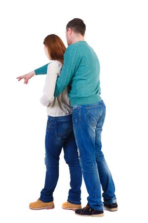 personas abrazadas: joven pareja señalando vista Volver wal (mujer y hombre). Vista posterior recogida de las personas. trasero vista de la persona. Aislado sobre fondo blanco. Un hombre en una chaqueta verde abrazó por detrás de la mujer y muestra su mano hacia abajo.