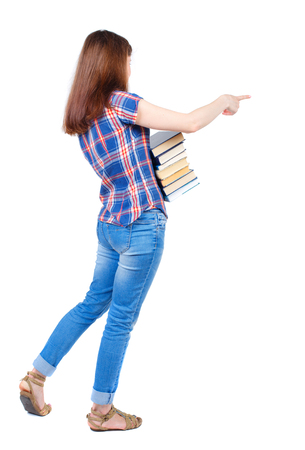 Girl carries a heavy pile of books. back view.  Rear view people collection.  backside view of person.  Isolated over white background. Girl in plaid shirt cancer is holding a stack of books and pointing her finger sideways.