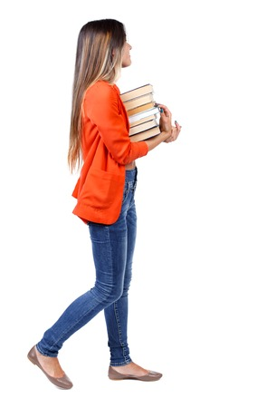 Girl comes with  stack of books. side view. Rear view people collection.  backside view of person.  Isolated over white background. girl in a red jacket goes to the side with a stack of books looking at what is to come. Stock Photo