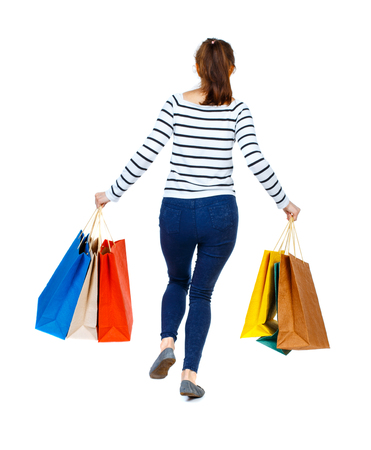 back view of a woman jumping with shopping bags. beautiful brunette girl in motion.  backside view of person.  Rear view people collection. Isolated over white background. Girl in a striped sweater runs away with paper bags in their hands.