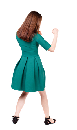 wimp: skinny woman funny fights waving his arms and legs. Isolated over white background. The slender brunette in a green short dress has her hands. Stock Photo
