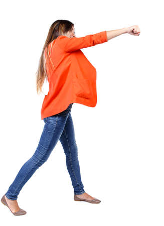 back view of woman funny fights waving his arms and legs. Rear view people collection. backside view of person.  Isolated over white background. girl in a red jacket stands sideways and strike his hand.