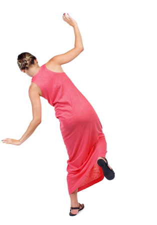 Balancing young woman.  or dodge falling woman. Rear view people collection.  backside view of person.  Isolated over white background. A slender woman in a long red dress is trying to stand on the leg. Stock Photo