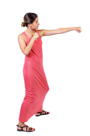skinny woman funny fights waving his arms and legs. Isolated over white background. A slender woman in a long red dress fulfills hands. Stock Photo