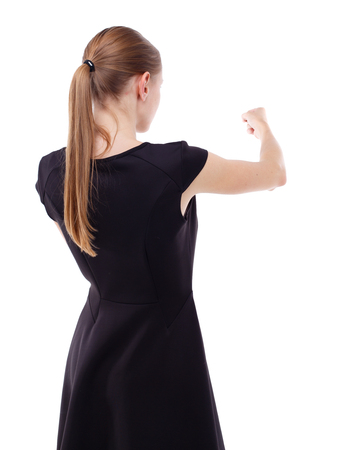 wimp: skinny woman funny fights waving his arms and legs. Isolated over white background. Blonde in a short black dress punches. Stock Photo