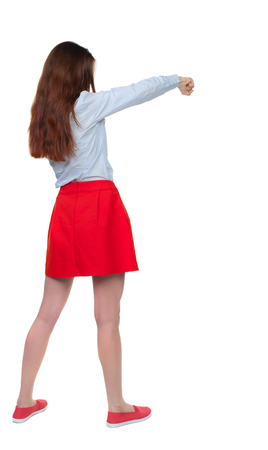 wimp: skinny woman funny fights waving his arms and legs. Isolated over white background. Long-haired brunette in red skirt boxing.
