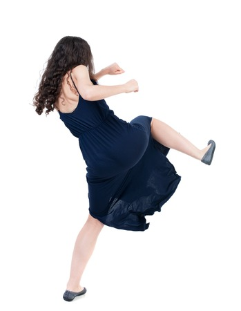 skinny woman funny fights waving his arms and legs. Isolated over white background. The dark curly girl in blue evening dress kicks.