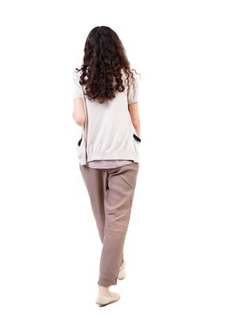 back view of walking  curly woman.  backside view of person.  Rear view people collection. Isolated over white background. Long-haired curly girl is waving his arms. Stock Photo