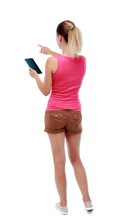 back view of pointing young beautiful  woman and using a mobile phone. girl  watching. Rear view people collection.  backside view of person.  Isolated over white background. Sport blond in brown shorts reading an e-book and shows up finger.