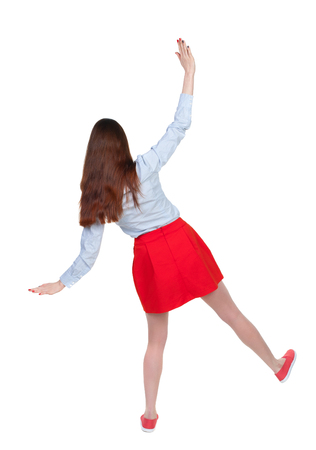 Balancing young woman.  or dodge falling woman. Rear view people collection.  backside view of person.  Isolated over white background. Long-haired brunette waves his arms in a red skirt falling.