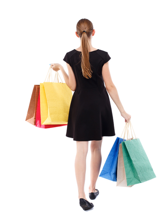 back view of going  woman  with shopping bags . beautiful girl in motion.  backside view of person.  Rear view people collection. Isolated over white background. Blonde in a short black dress shopping.