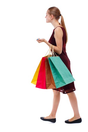 side view of going  woman  with shopping bags . beautiful girl in motion.  backside view of person.  Rear view people collection. Isolated over white background. Slim blonde in a burgundy dress carries colorful shopping bags.