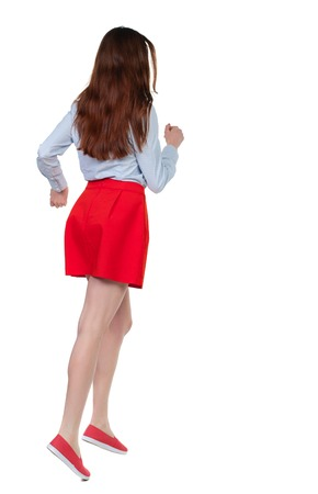 side view of running  woman. beautiful girl in motion. backside view of person.  Rear view people collection. Isolated over white background. Long-haired brunette in red skirt quickly escapes.