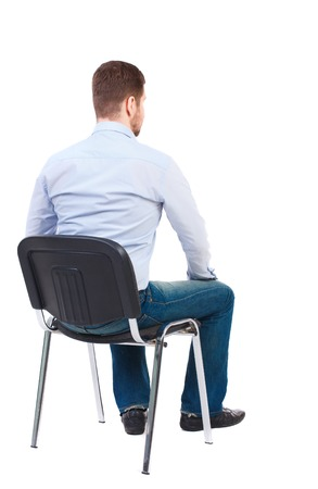 looking at view: back view of business man sitting on chair.  businessman watching. Rear view people collection.  backside view of person.  Isolated over white background. Bearded businessman in white shirt sits on a chair and looking forward.