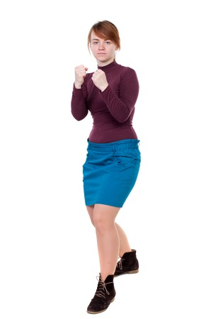 skinny woman funny fights waving his arms and legs. Isolated over white background. Girl with red hair standing in a boxing pose and looks in the frame. Stock Photo