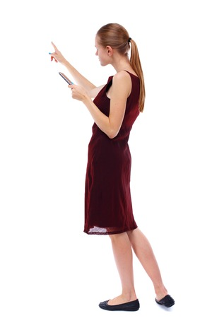 girl in burgundy dress: back view of pointing young beautiful  woman and using a mobile phone. girl  watching. Rear view people collection.  backside view of person.  Isolated over white background. Slim blonde in a burgundy dress that tells the reading from the tablet.