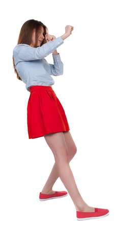 wimp: skinny woman funny fights waving his arms and legs. Isolated over white background. Long-haired brunette in red skirt leaned protected from impact.