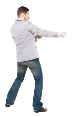 back view of standing man pulling a rope from the top or cling to something.  Rear view people collection.  backside view of person.  Isolated over white background. A guy in a gray jacket waving his arms. Stock Photo
