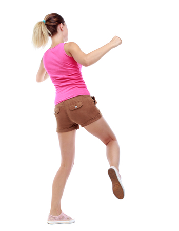 wimp: back view of woman funny fights waving his arms and legs. Rear view people collection. backside view of person.  Isolated over white background. Sport blond in brown shorts hit someone Stock Photo