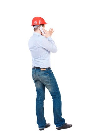 Backview of business man in construction helmet stands and enjoys tablet or using a mobile phone. Standing young guy. Rear view people collection.  backside view of person.  Isolated over white background. businessman in a white shirt and a construction h