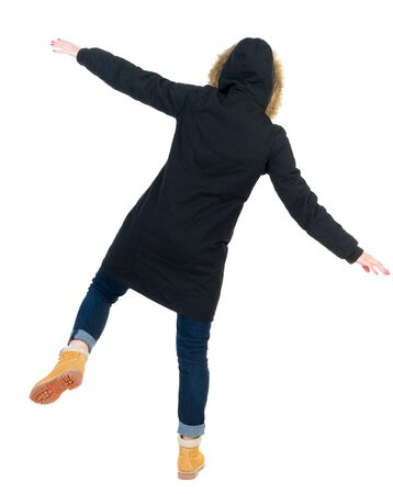 balances: Back view woman in winter jacket  Balances waving his arms.   Standing young girl in parka. Rear view people collection.  backside view of person.  Isolated over white background. Girl in warm winter black jacket falls to the side. Stock Photo