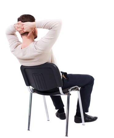 behind: back view of business man sitting on chair.  businessman watching. Rear view people collection.  backside view of person.  Isolated over white background. The bearded man in a white warm sweater sits on a chair with his hands behind his head. Side view.