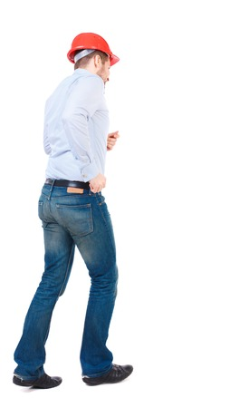 diagonally: Back view of running engineer in helmet. Walking guy in motion. Rear view people collection. Backside view of person. Isolated over white background. Bearded businessman in a white shirt and a helmet runs diagonally.
