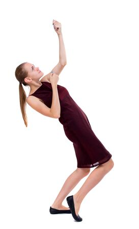 back view of standing girl pulling a rope from the top or cling to something. girl  watching. Rear view people collection.  backside view of person.  Isolated over white background. A girl in a burgundy dress pulls the top rope. Stock Photo