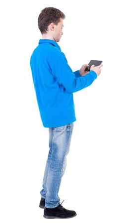 back view of business man uses mobile phone.    rear view people collection. Isolated over white background. backside view of person. Curly boy in blue jacket plays games on the tablet. Stock Photo