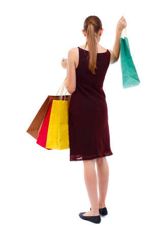 girl in burgundy dress: back view of going  woman  with shopping bags . beautiful girl in motion.  backside view of person.  Rear view people collection. Isolated over white background. Slim blonde in a burgundy dress holding shopping in their hands.