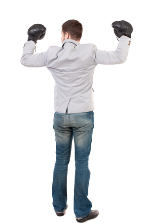 wimp: businessman with boxing gloves in fighting stance. Isolated over white background. Rear view people collection.  backside view of person. Man in gray suit and boxing gloves celebrating the victory.