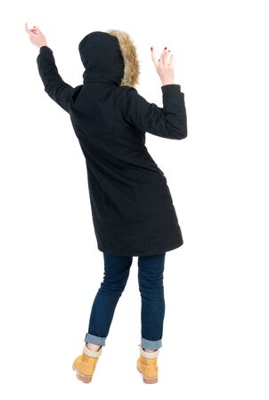 Back view woman in winter jacket  Balances waving his arms.   Standing young girl in parka. Rear view people collection.  backside view of person.  Isolated over white background. The girl in warm winter jacket black dancing. Stock Photo