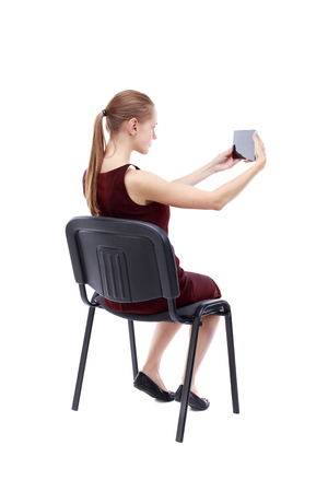 girl in burgundy dress: back view of woman sitting on chair and looks at the screen of the tablet.  Rear view people collection.  backside view of person.  Isolated over white background. A girl in a burgundy dress sitting on a chair and taking pictures Tablet.