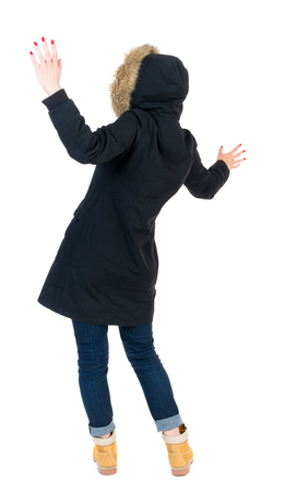 parka: Back view woman in winter jacket  Balances waving his arms.   Standing young girl in parka. Rear view people collection.  backside view of person.  Isolated over white background. The girl in warm winter jacket, black, surprised her arms.