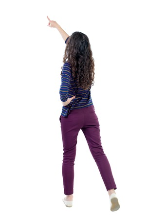pulled over: Back view of  pointing woman. beautiful girl. Rear view people collection.  backside view of person.  Isolated over white background. Long-haired curly girl in a blue sweater pulled up.
