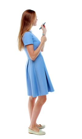 back view of writing beautiful woman. Young girl in dress. Rear view people collection.  backside view of person. Isolated over white background. Skinny girl in a blue dress and pen writes on the blackboard.