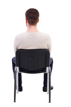 Vista posteriore di uomo d'affari seduto sulla sedia. Guardare l'uomo d'affari. Raccolta persone vista posteriore. Vista posteriore della persona. Isolato su sfondo bianco. L'uomo barbuto in un maglione caldo bianco si siede su una sedia e vede l'ora di avanzare.