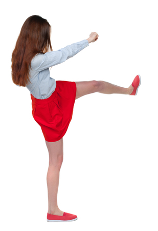 cancer foot: skinny woman funny fights waving his arms and legs. Isolated over white background. Long-haired brunette in red skirt is cancer and has foot. Stock Photo