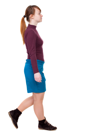 back view of walking  woman. beautiful blonde girl in motion.  backside view of person.  Rear view people collection. Isolated over white background. The red-haired girl in a blue skirt passes. Stock Photo