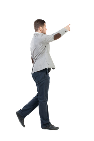 Back view of going  business man pointing. walking young guy . Rear view people collection.  backside view of person.  Isolated over white background. The bearded man in a gray jacket is pointing to the sky with his finger. Stock Photo