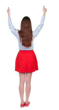 Back view of  woman thumbs up. Rear view people collection. backside view of person. Isolated over white background. Long-haired brunette in red skirt lifted thumbs up.