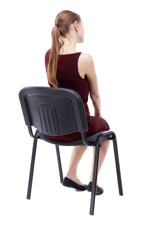 listening back: back view of young beautiful  woman sitting on chair.  girl  watching. Rear view people collection.  backside view of person.  Isolated over white background. A girl in a burgundy dress sitting on a chair listening to a lecture.