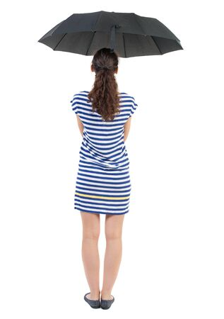 young woman in  dress under an umbrella. Rear view people collection.  backside view of person.  Isolated over white background. Swarthy girl in a checkered dress standing under an umbrella. Stock Photo