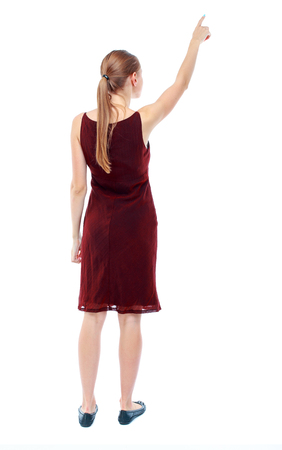 sleeveless dress: Back view of  pointing woman. beautiful girl. Rear view people collection.  backside view of person.  Isolated over white background. The girl in the maroon sleeveless dress shows a finger to the sky.