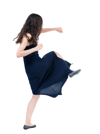 wimp: skinny woman funny fights waving his arms and legs. Isolated over white background. The dark curly girl in blue evening dress fights.