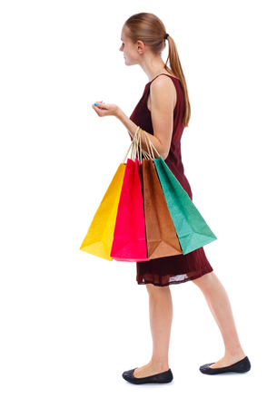 side view of going  woman  with shopping bags . beautiful girl in motion.  backside view of person.  Rear view people collection. Isolated over white background. Slim blonde in a burgundy dress shops. Stock Photo