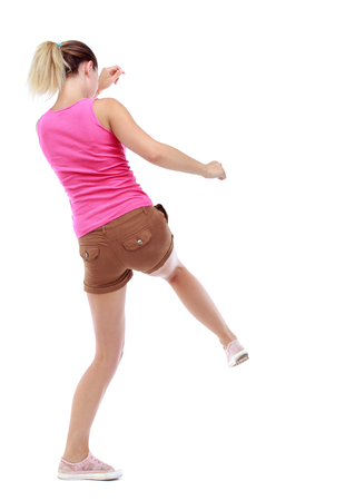 wimp: back view of woman funny fights waving his arms and legs. Rear view people collection. backside view of person.  Isolated over white background. Sport blond in brown shorts hit his foot.