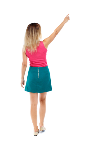 Back view of  pointing woman. beautiful girl. Rear view people collection.  backside view of person.  Isolated over white background. Blonde in a red sweater and green skirt went off pointing to the sky.