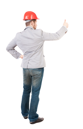 Back view of  business man shows thumbs up.   Rear view people collection. cheerful office worker shows positive emotions.  backside view of person.  Isolated over white background. A guy in a gray jacket and an orange helmet stands with his arms crossed. Фото со стока